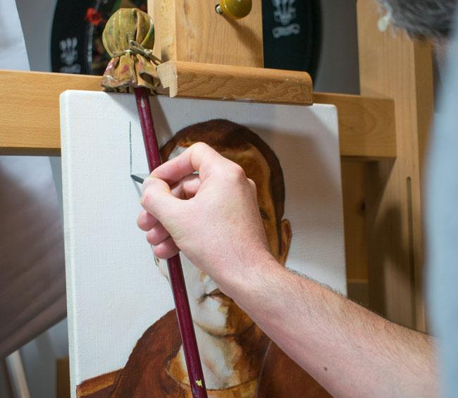 Mahlstick on easel with person painting