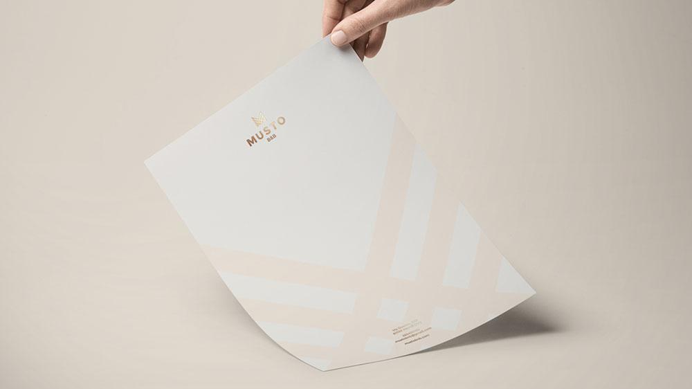 A hand holds a piece of paper with a gold foil Musto logo and pink diagonal stripes