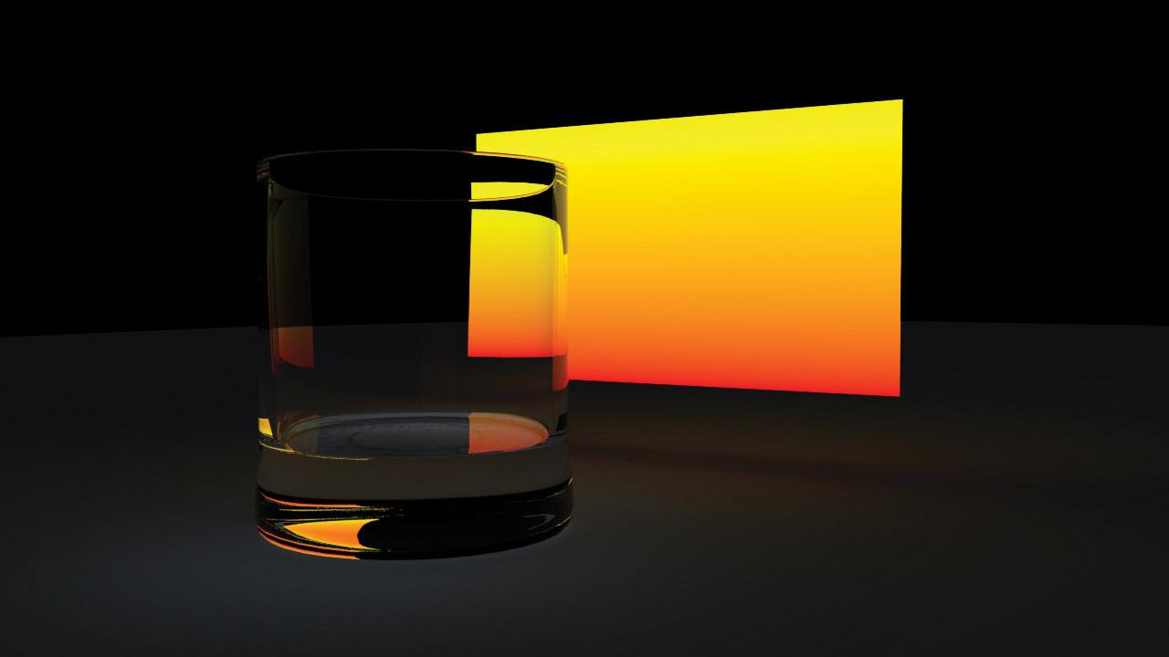 A glass tumbler in front of an illuminated screen