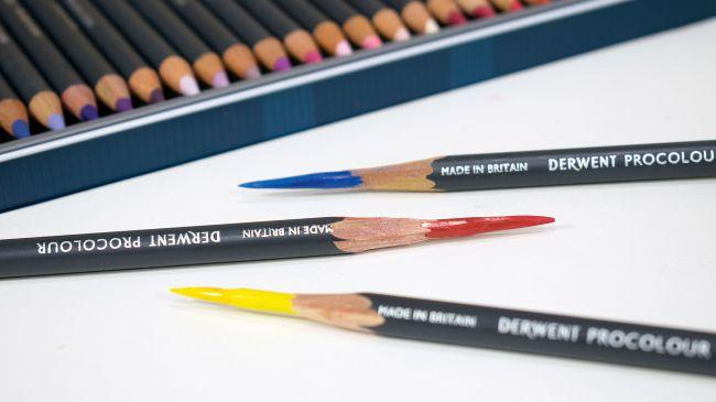 Three coloured Derwent Procolour pencils with the edge of the tin behind