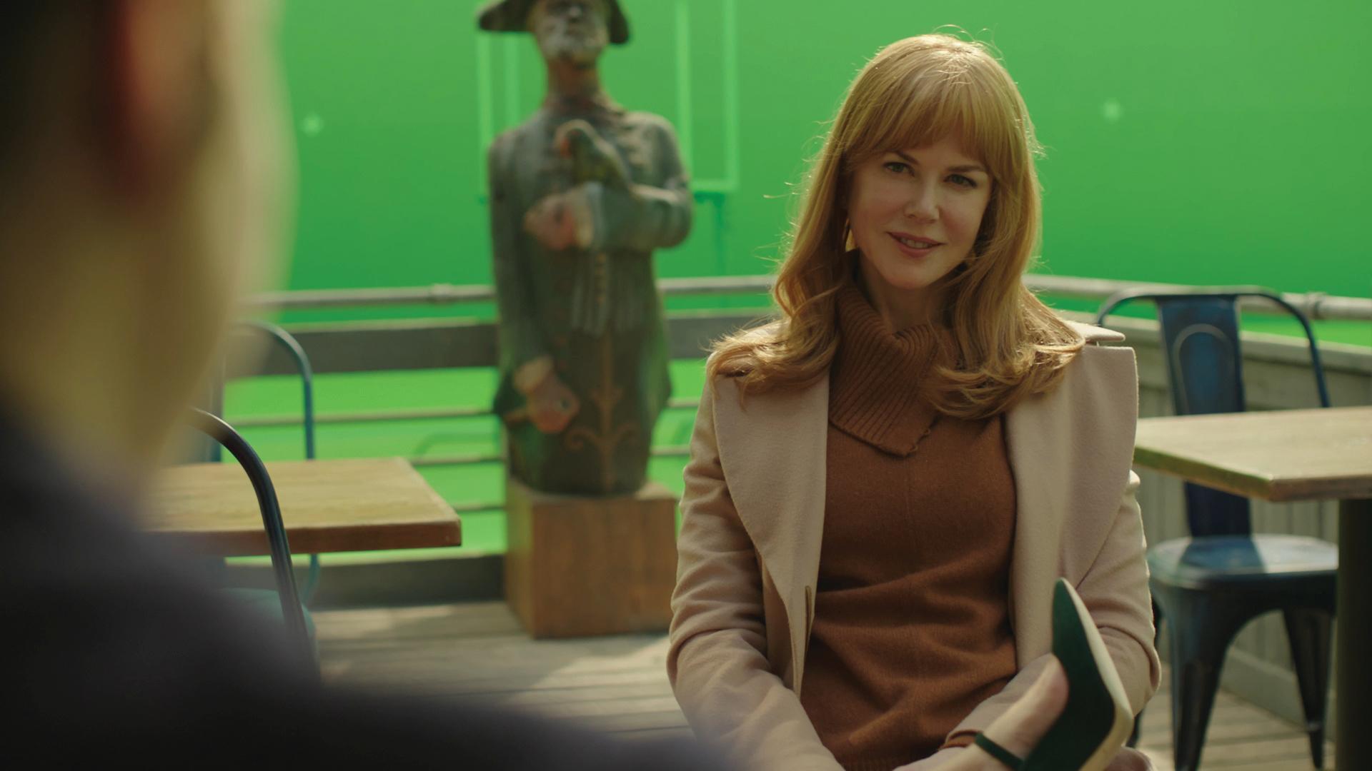 Nicole Kidman sitting on a green screen cafe set