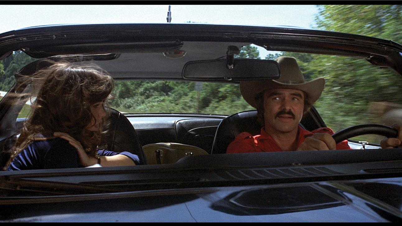 A scene from Smokey and the Bandit of Burt Reynolds driving a car next to Sally Field